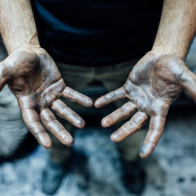 A male industrial worker showing the palms of his hands covered in oil and chemical residue