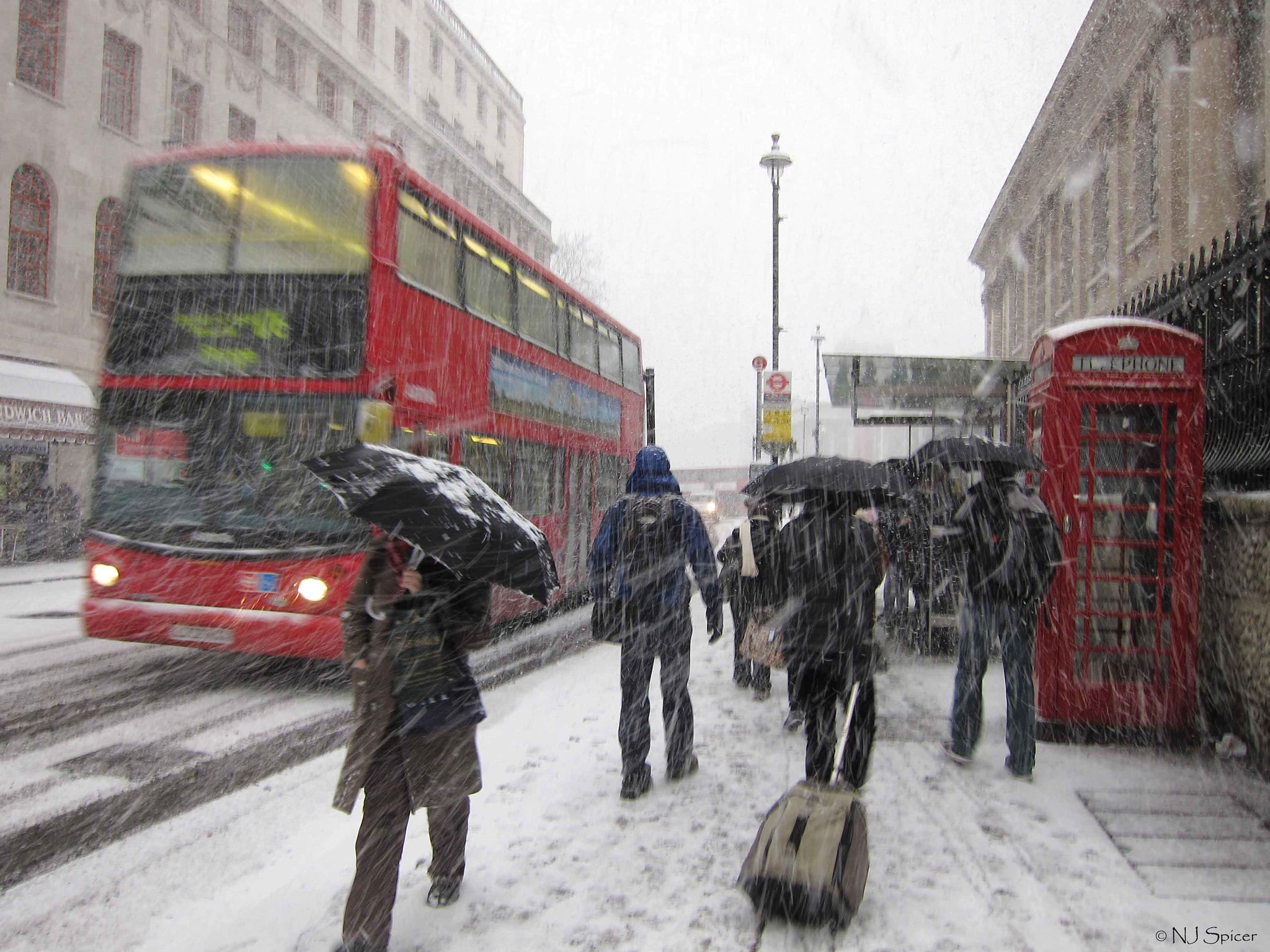 Commuters struggle through the snow on a London street as a red london bus drives past, the sleet and snow pelts down